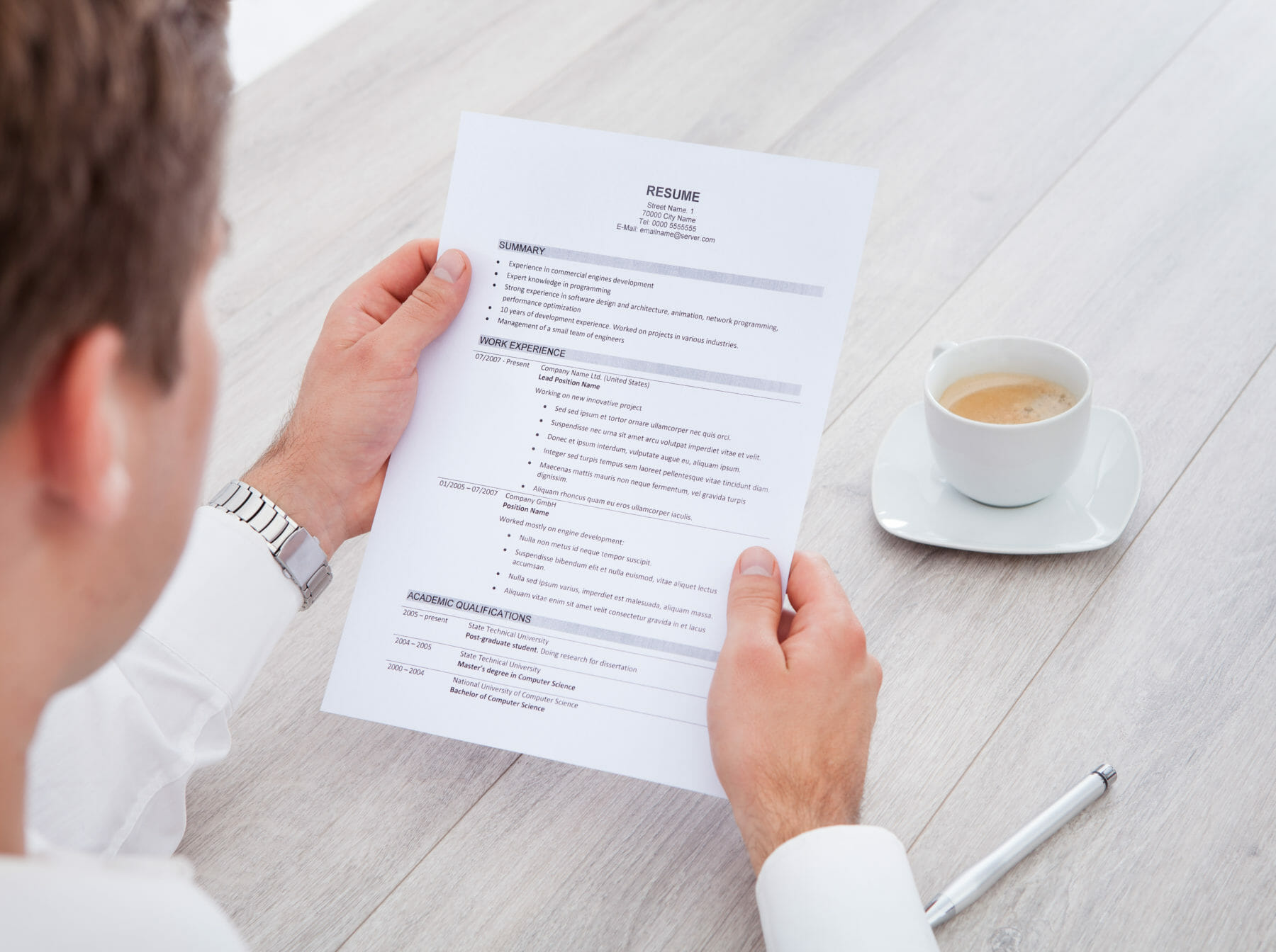 close up of businessman reading resume with tea cup on desk